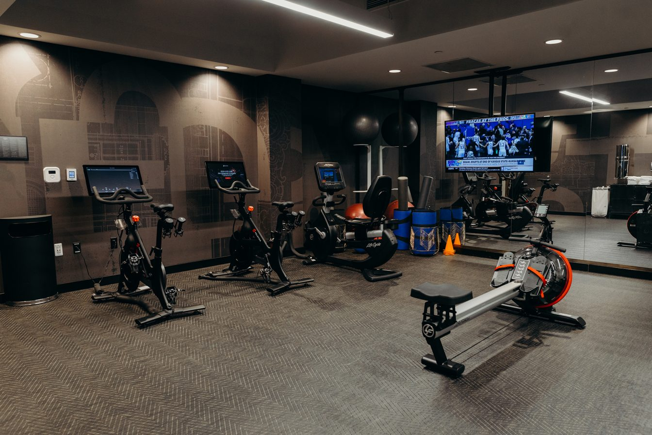 Several exercise bikes, a rowing machine, and a tv, at the hotel fitness center in downtown Detroit.