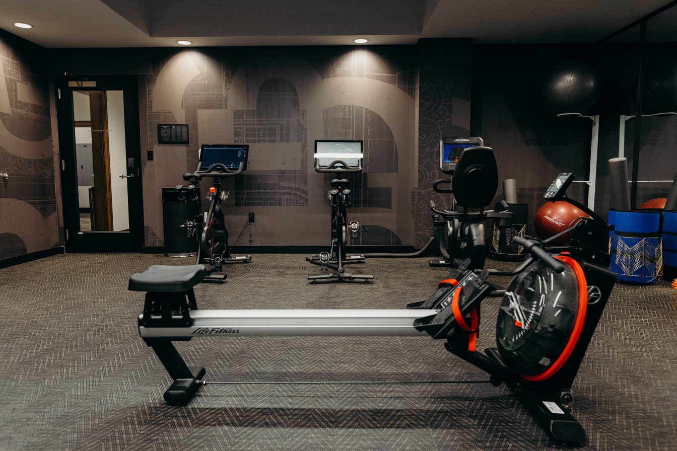 Recumbent and upright exercise bikes and a rowing machine at the fitness center of the Detroit hotel.