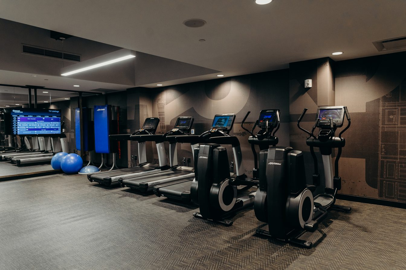 Treadmills, ellipticals, exercise mats, bosu balls, and a tv at the fitness center of the Detroit hotel.